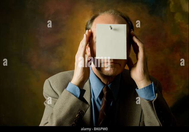 man in suit and tie with note covering face - Stock Image
