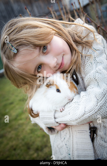 young girl playing with a cavy in the garden - Stock Image