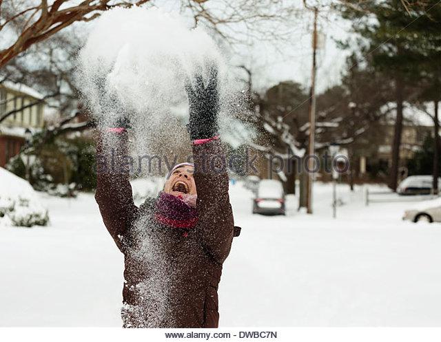Teenage girl throwing powdered snow mid air - Stock Image