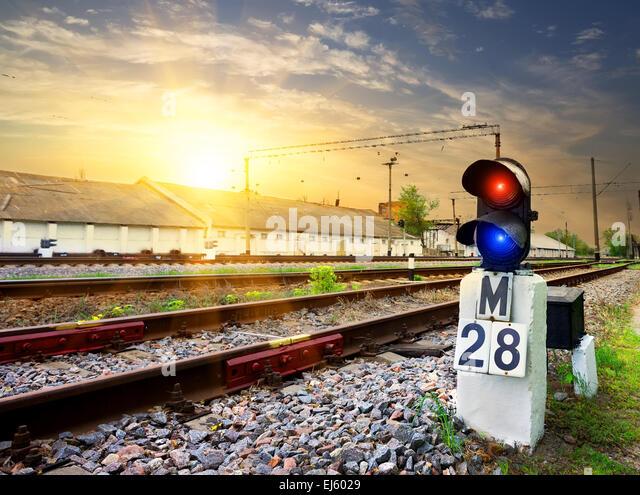 Railway semaphore near industrial station at sunset - Stock Image