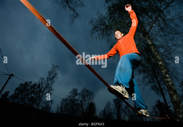 A man balancing on a cord. - Stock Image