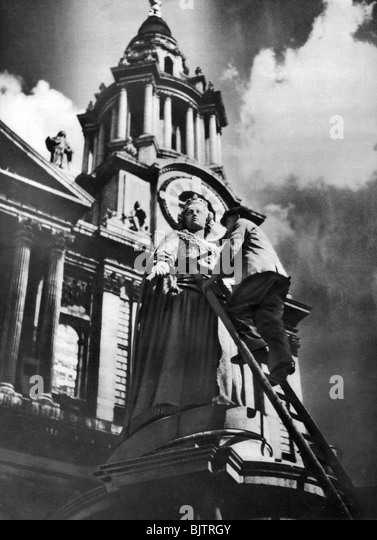 Cleaning the statue of Queen Anne as part of King George V's silver jubilee celebrations, 1935. - Stock Image