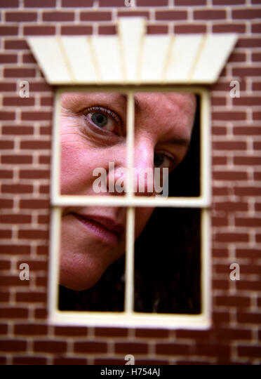 Woman peering through the window of a dolls house, Alton, Hampshire, UK. - Stock Image