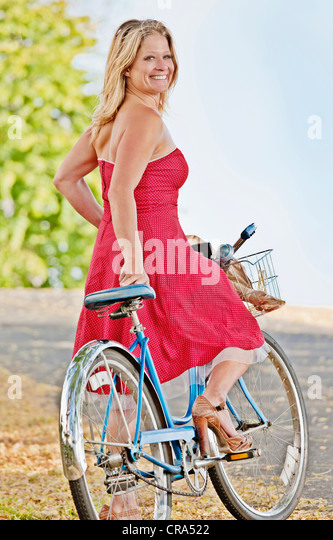 Woman riding bicycle on dirt road - Stock Image