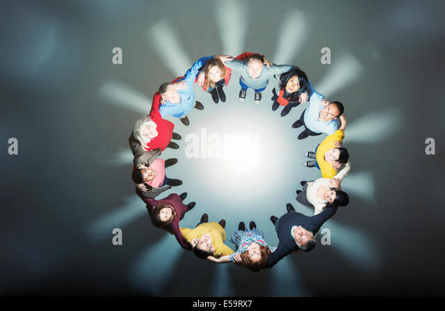 Business people forming huddle around bright light - Stock Image