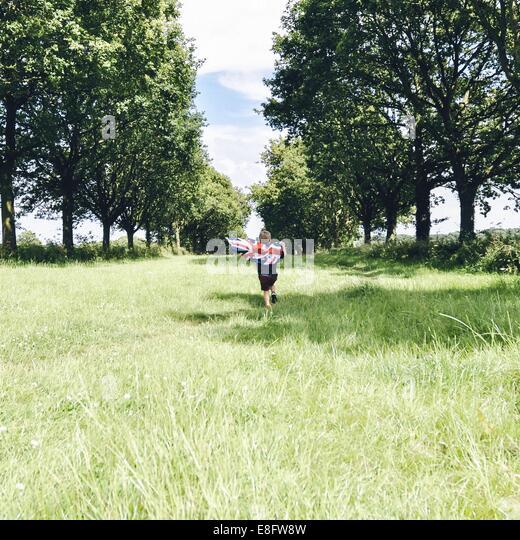 Boy running through field holding Union Jack flag - Stock Image
