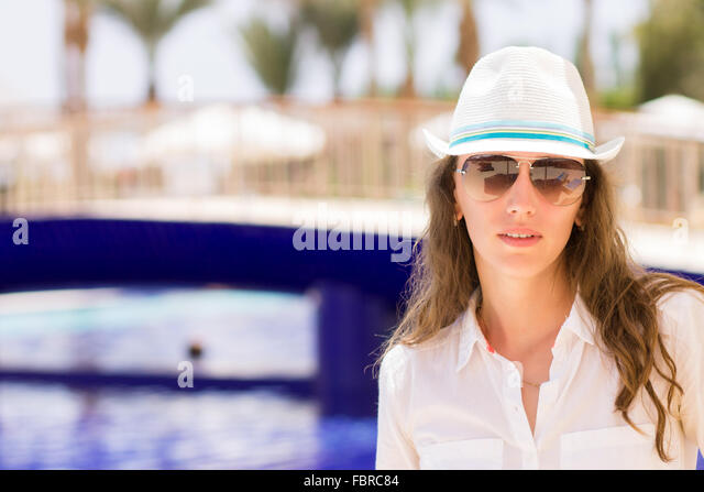 Young beautiful girl stands near the swimming pool. Pretty woman on summer holidays at tropical resort - Stock Image