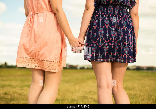 Two young women walking hand in hand, close-up - Stock Image