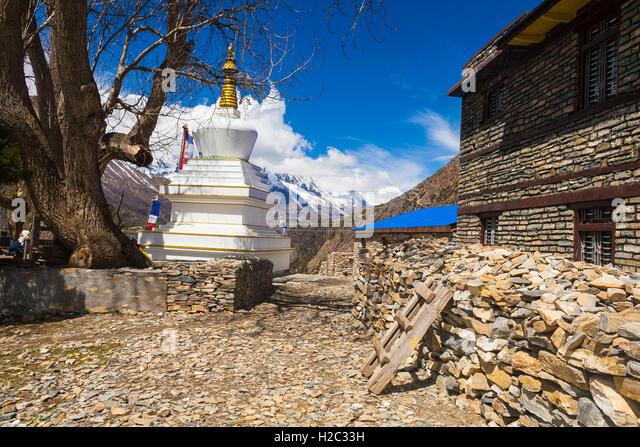 Tibetan prayer stupa or prayers place of the faithful Buddhists in center Mountains Village. Blue Sky Background. - Stock Image