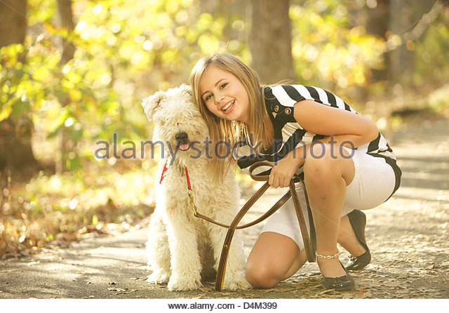 Smiling girl walking dog in forest - Stock Image