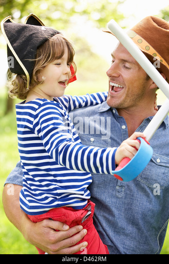 Father Playing Exciting Adventure Game With Son In Summer Field - Stock Image