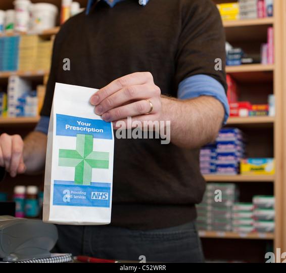 pharmacist handing over prescription at chemist - Stock Image