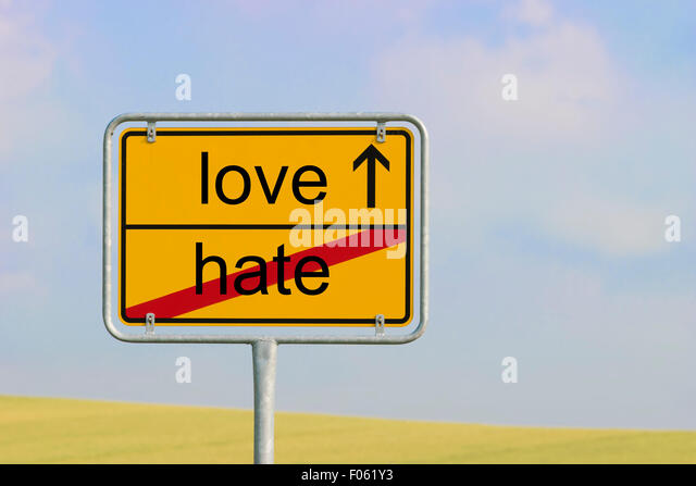 Yellow town sign with text 'hate love' - Stock Image