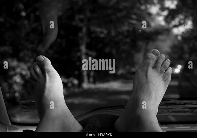 A man with his feet up on the dashboard of the passenger side of a car traveling through country lanes. - Stock Image