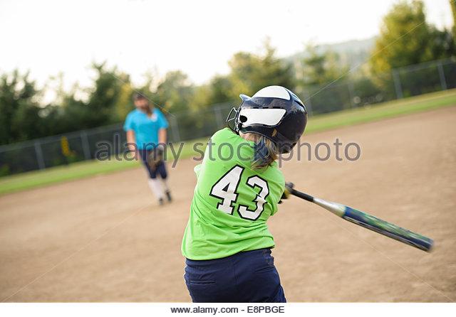 Girl (10-12) playing baseball - Stock-Bilder