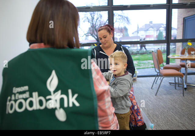 A family receiving advice at Epsom Foodbank, food donations for families suffering from financial difficulty, Surrey, - Stock Image