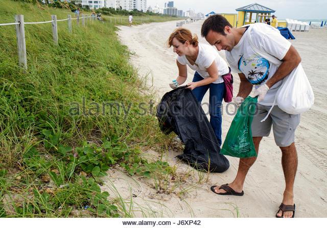 Miami Beach Florida Coastal Cleanup Day volunteer litter trash pollution public beach pick up man woman couple - Stock Image