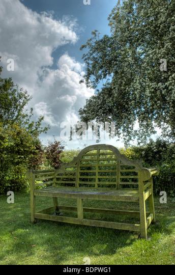 A garden bench under flowering tree blossom and a blue sky - Stock-Bilder