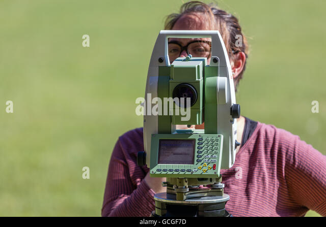 Female surveyor conducting a survey with the Leica Total Station - Stock Image