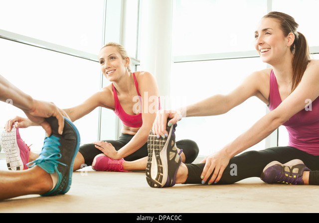 Friends stretching in gymnasium - Stock Image