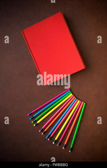 Wooden writer desktop with colorful pencil and red empty cover book, vertical frame - Stock Image