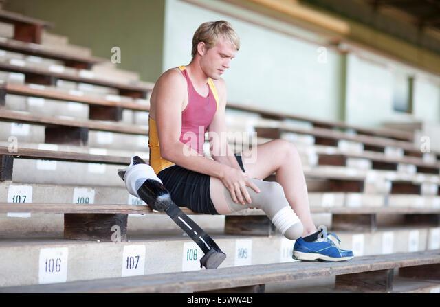 Sprinter preparing, putting on prosthetic leg - Stock Image