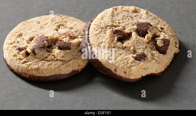 Two chocolate chunk & hazelnut dipped biscuits - Stock Image