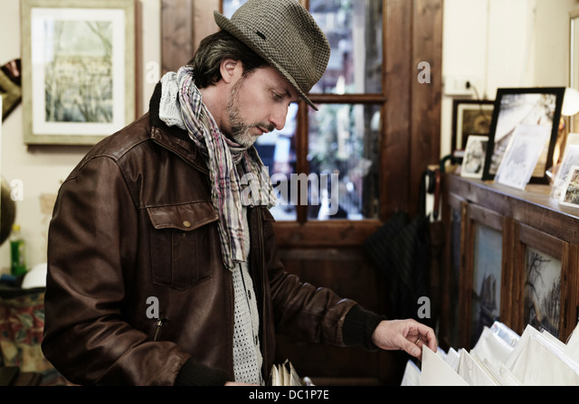 Mid adult man browsing in antique shop - Stock Image