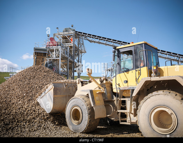 Digger scooping pile of stones in quarry - Stock Image
