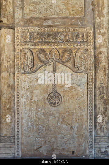 Ornate engraved stone wall with floral patterns and calligraphy, Ibn Tulun Mosque, Cairo, Egypt - Stock Image