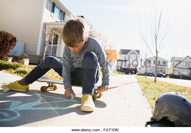 Boy on skateboard drawing on sidewalk with chalk - Stock-Bilder