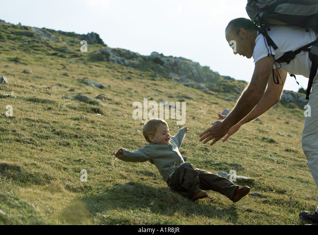 Boy falling as father reaches for him - Stock Image