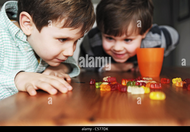Boys playing with candy at table - Stock Image