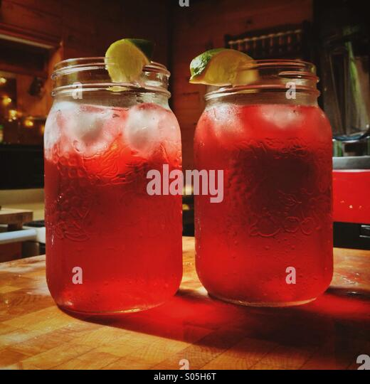 Two large jars of red iced hibiscus tea drinks on chopping block in kitchen - Stock Image