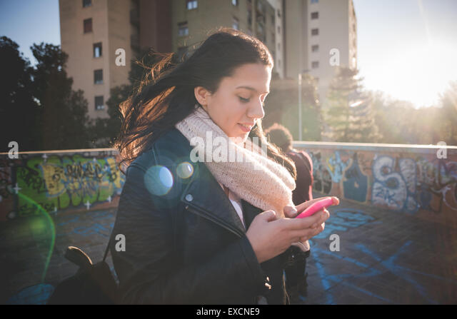 young beautiful long hair woman in town during sunset backlight using a smartphone - Stock Image