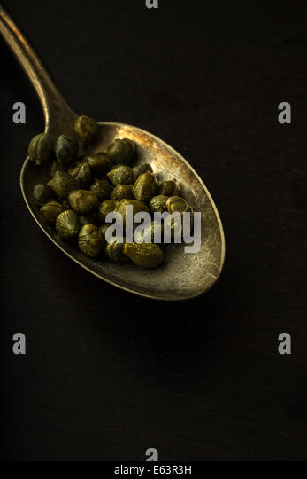 An old silver spoon full of capers with dark and moody lighting. - Stock Image
