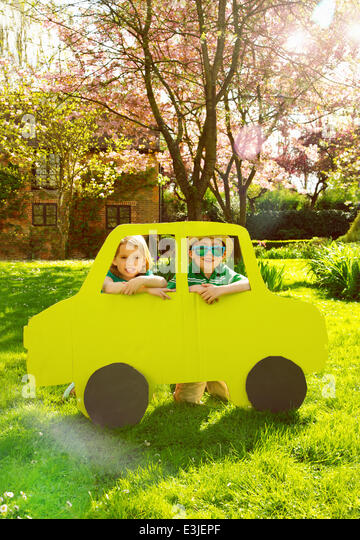 Boy and Girl Looking out of Cardboard Car Window - Stock Image
