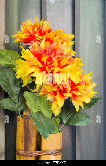 humble bouquet of fabric flowers on bamboo tube - Stock Image