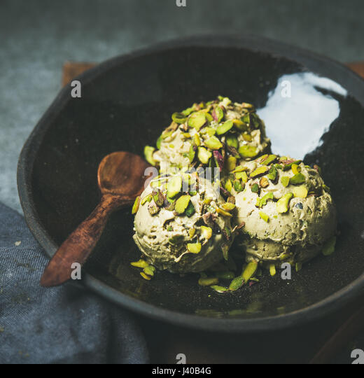 Homemade pistachio ice cream scoops with crashed nuts, square crop - Stock Image
