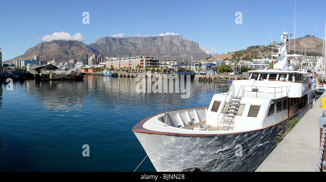 Motor cruiser in the Victoria and Alfred Waterfront harbour and Table Mountain in Cape Town, South Africa - Stock Image