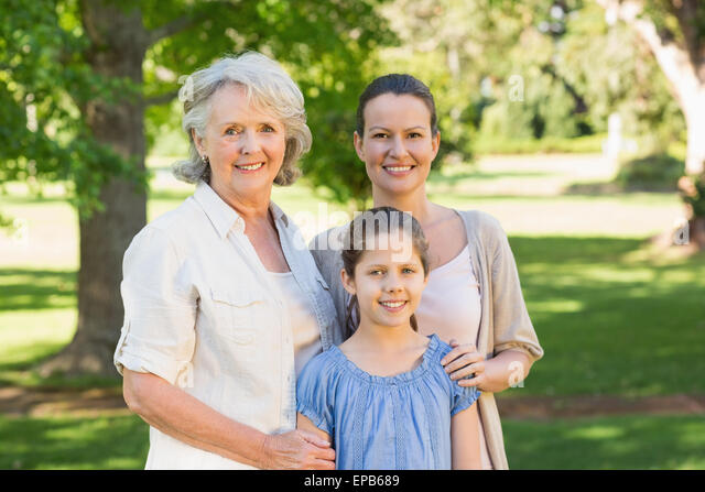 Smiling woman with grandmother and granddaughter at park - Stock Image