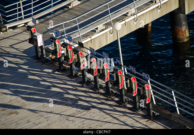 Line of red telephones for international calls on cruise pier - Stock Image