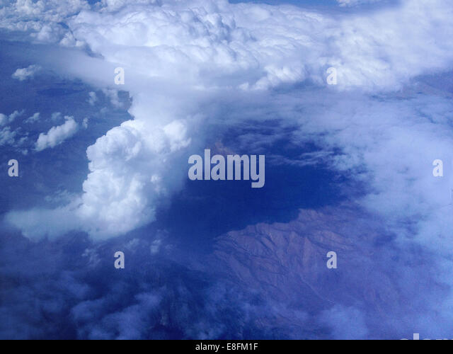 USA, California, Cumulus clouds and mountains from above - Stock Image