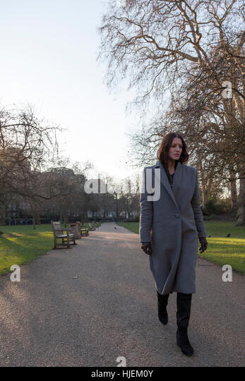Attractive dark haired woman walks alone through a park - Stock Image