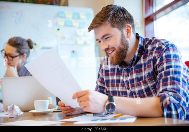 Happy young businessman reading paper in office - Stock Image