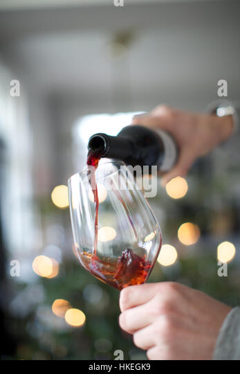 human hands pouring red wine in glass. wine bottle, alcohol, celebration, wine glass. - Stock-Bilder