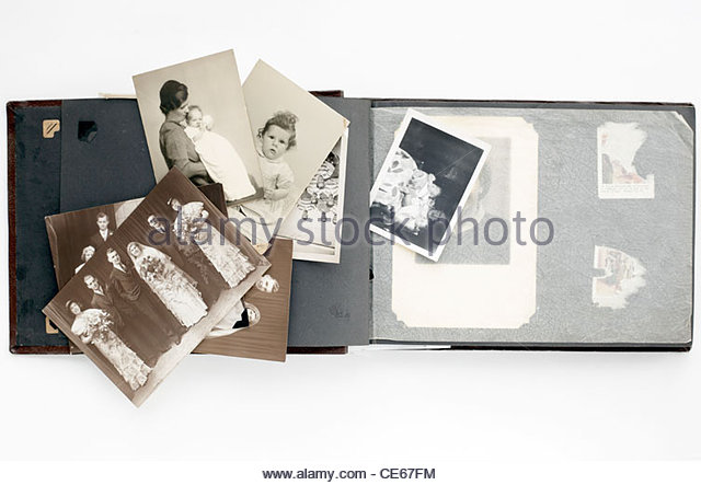 family photo album with loose images from 1920s and 1950s - Stock Image