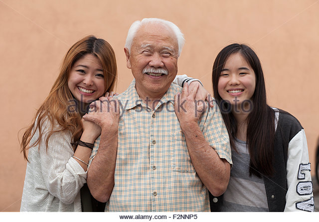 Grandfather and granddaughters smiling outdoors - Stock Image