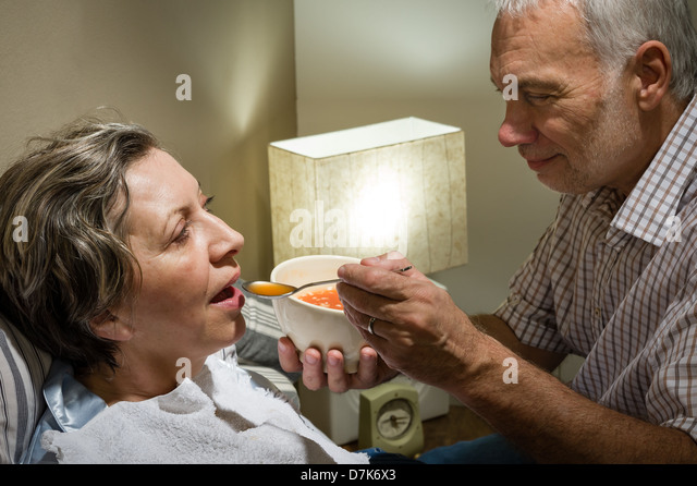 Loving retired husband feeding his ill wife with soup - Stock-Bilder