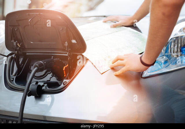 Male hands holding a map on the vehicle hood - Stock Image